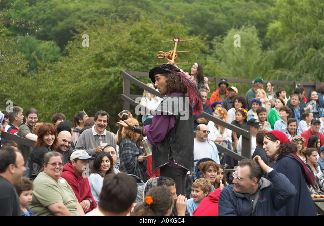 Young man in medieval dress stands among the crowd at the NY Renaissance Faire NY USA - Stock Image