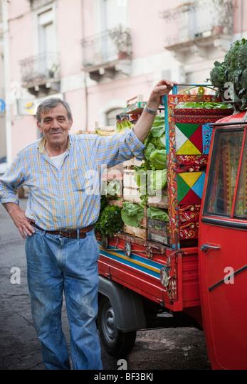 fruit vendor next to his ape-transporter - Stock Image