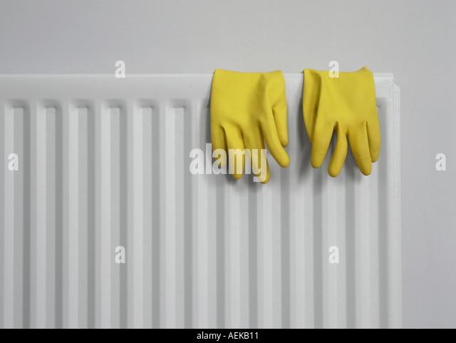 Yellow rubber gloves on grey radiator - Stock-Bilder
