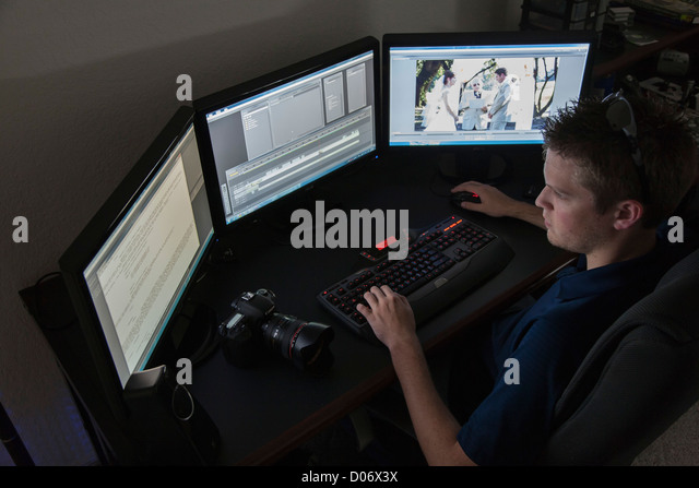 Young adult male videographer editing a wedding video on his computer system - Stock Image