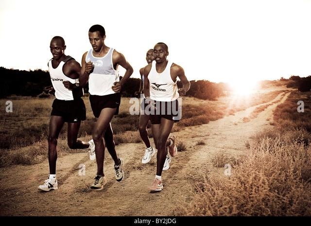 Kenyan marathon runners at sunset - Stock Image