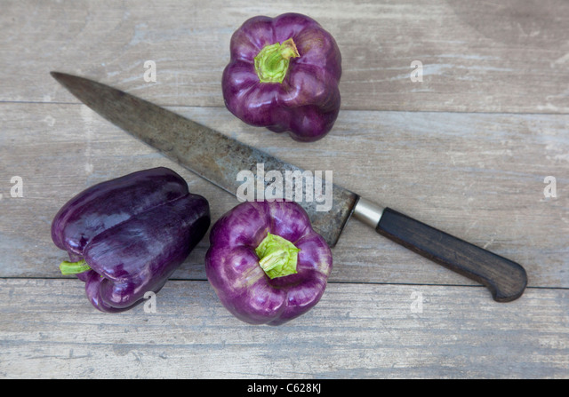 purple sweet peppers with knife - Stock Image