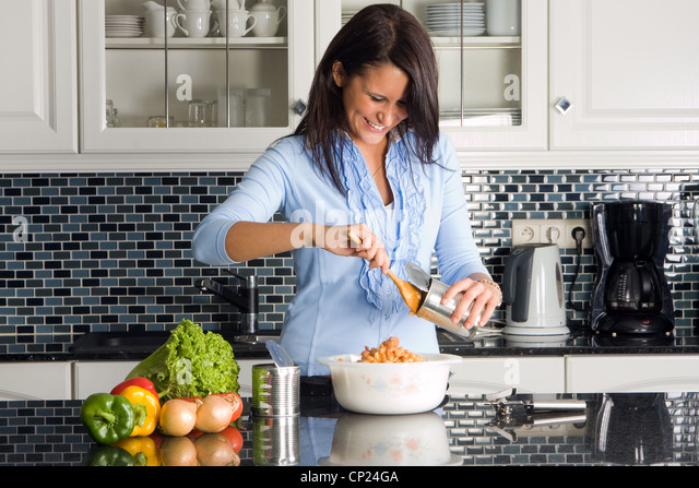Young housewife preparing dinner out of a can - Stock Image