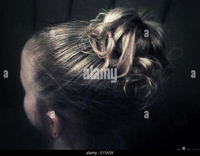 A young girl's high curly ponytail seen from behind. - Stock Image