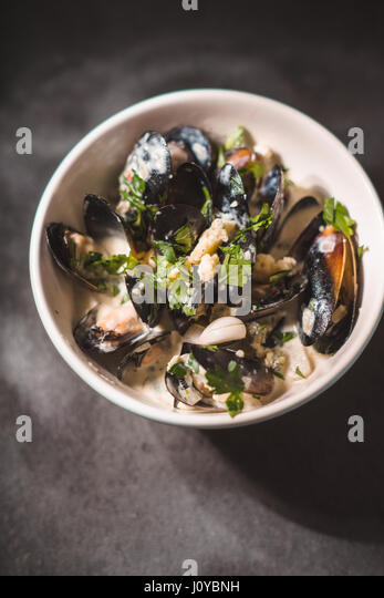 Mussels in sashes in sauce in a bowl on black slate - Stock Image