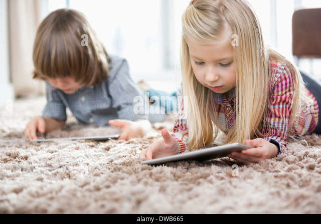 Cute girl and brother using digital tablets on rug in living room - Stock Image
