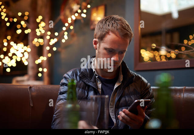 Man Sitting Inside Cafe Sending Text Message - Stock Image