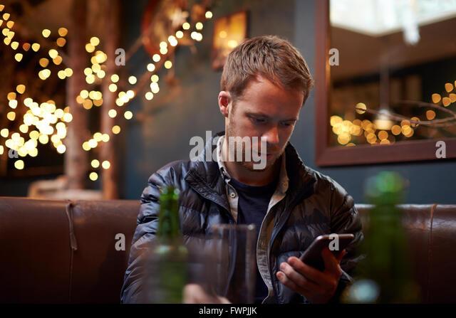 Man Sitting Inside Cafe Sending Text Message - Stock Image