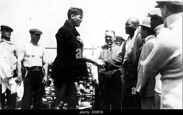 Boxers Jack Johnson (center left) and Jess Willard (center right), surrounded by other industry members, shake hands - Stock Image