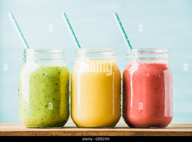Freshly blended fruit smoothies of various colors and tastes - Stock Image