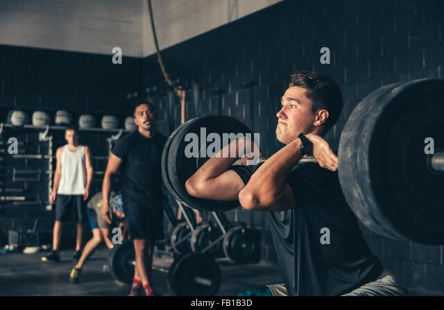 Man and trainer training with barbell in gym - Stock Image