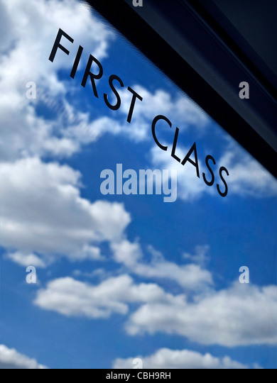 Concept ...First Class sign on window of railway carriage with infinity blue sky and clouds behind - Stock-Bilder