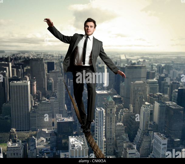 Businessman is balancing on a rope - Stock-Bilder