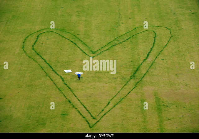 Germany,Berlin, giant heart design on lawn with a person standing inside - Stock Image