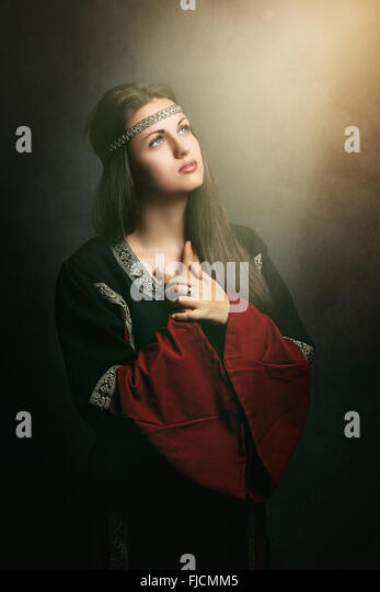 Beautiful medieval woman praying in soft holy light . Historical and religion - Stock-Bilder