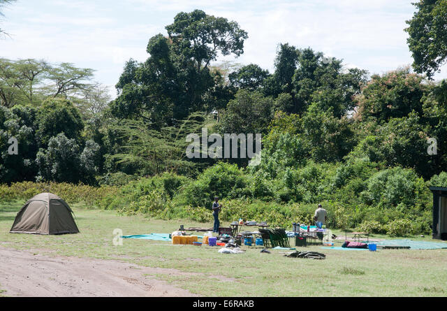 Staff working at striking camp and collecting kit on camp site near Makalia Falls in Lake Nakuru National Park Kenya - Stock Image