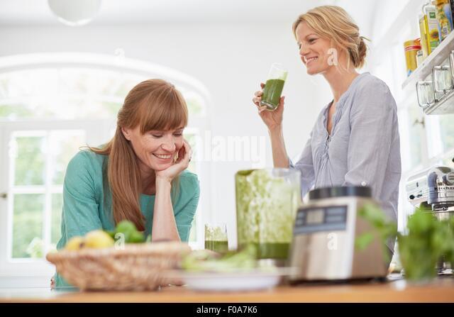 Women drinking green vegan smoothie in kitchen - Stock Image