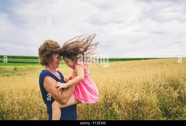 Mature women lifting up baby girl - Stock Image