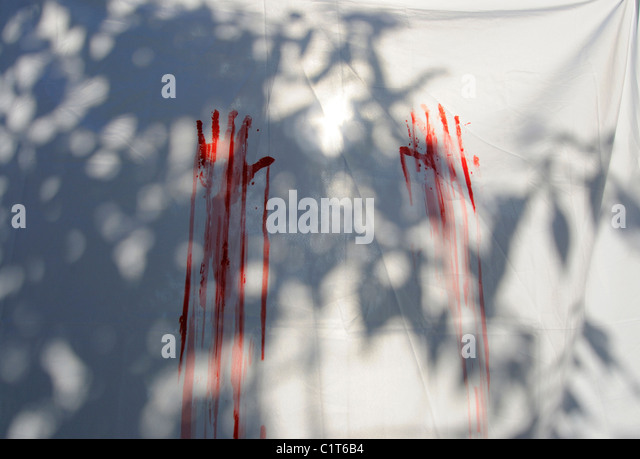 Red handprints on white sheet - Stock Image