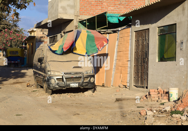 Dusty minivan on an unpaved road partly covered with a dusty sunshade in Mancora, Peru - Stock Image