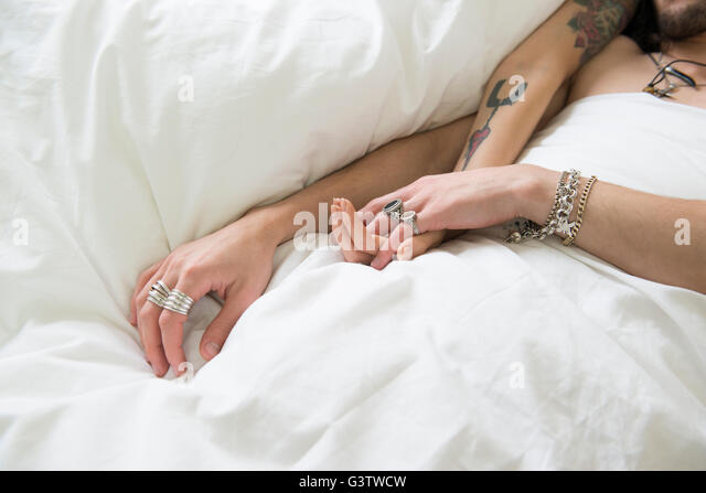 A young tattooed couple draping their arms across a duvet. - Stock-Bilder