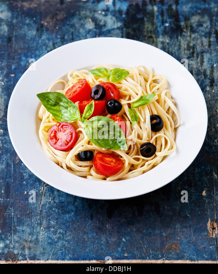 Pasta with tomato and basil on blue wooden background - Stock Image