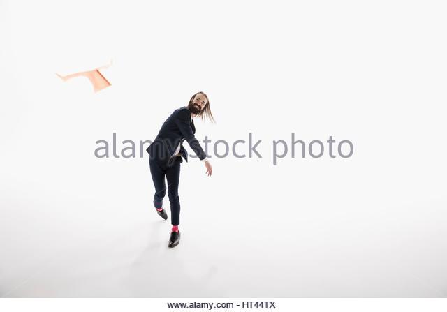 Portrait businessman throwing paper airplane against white background - Stock-Bilder
