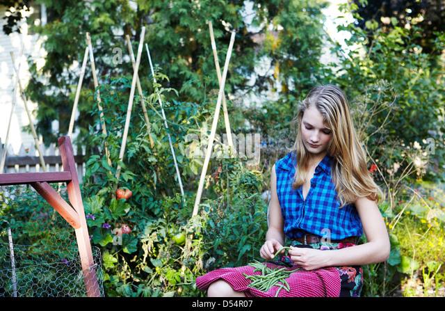 Teen girl in urban garden - Stock Image