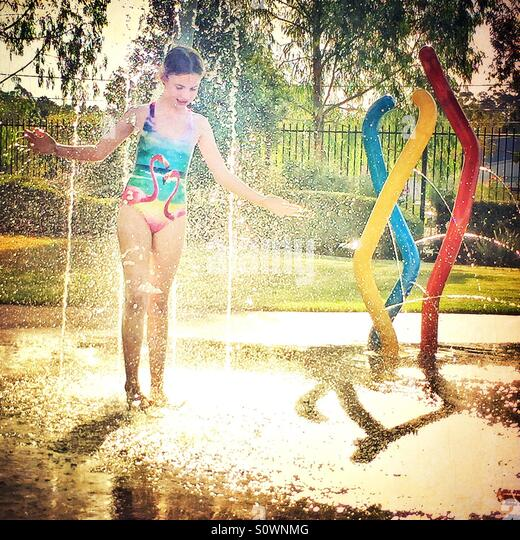 Girl in swimsuit playing in water fountain in summer - Stock Image