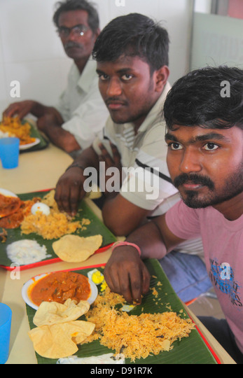 Singapore Little India Veerasamy Road restaurant Indian eating with hands Asian man banana leaf tray - Stock Image