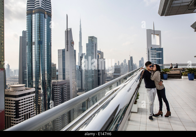 United Arab Emirates, Dubai, financial city center with Burj Khalifa, Asian couple kissing un rooftop of Sheraton - Stock Image