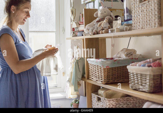 A pregnant woman in a nursery sorting out baby clothes. - Stock Image