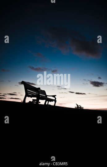 Silhouettes of empty park benches against the skyline of a twilight sky, UK - Stock Image