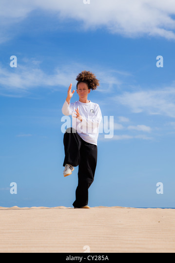 Young attractive woman making Thai-chi movements in the dunes by the ocean - Stock Image