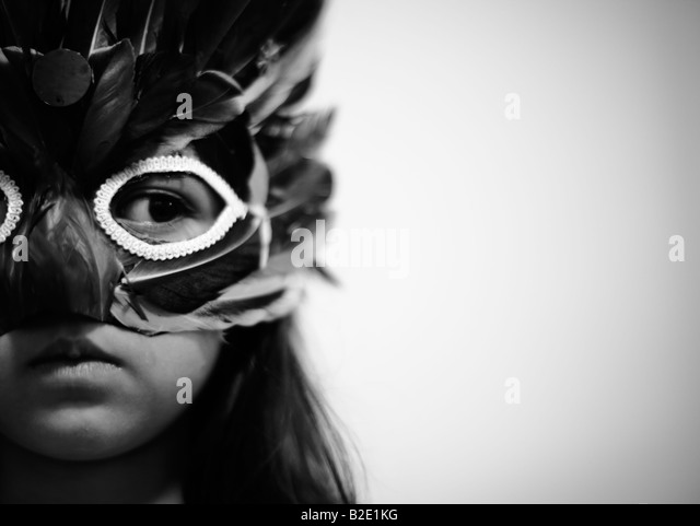 Five year old girl wears a feather costume mask - Stock Image
