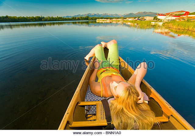 Woman relaxes in a canoe on Six Mile Lake near Anchorage Alaska during Summer - Stock Image