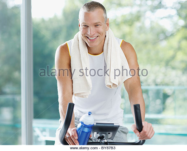 Smiling man sitting on stationary bicycle - Stock Image