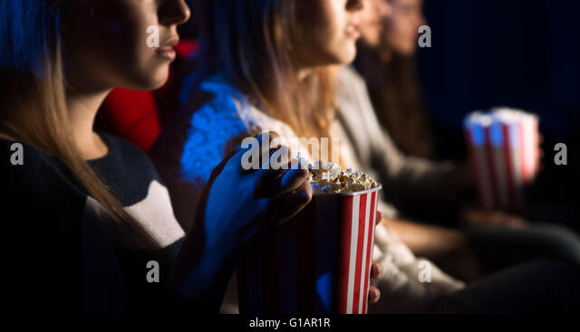Teenager friends at the cinema watching a movie together and eating popcorn, beautiful girl on foreground, movies - Stock-Bilder