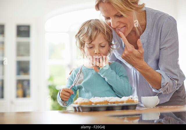 Mother and son making cupcakes in kitchen - Stock Image