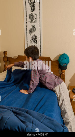 Young Korean/American boy making his bed.   MR ©Myrleen Pearson - Stock-Bilder