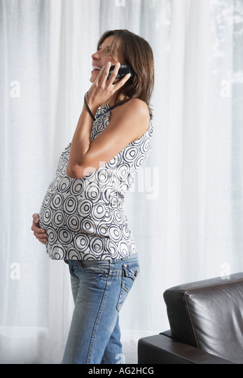 Pregnant woman using mobile phone in living room - Stock Image