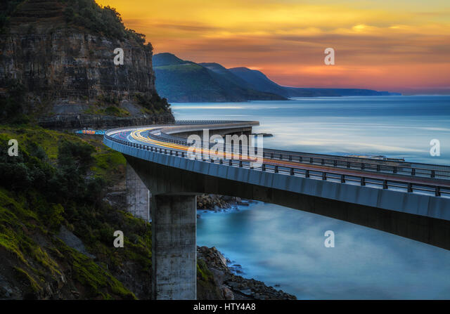 Sunset over the Sea cliff bridge along Australian Pacific ocean coast with lights of passing cars near Sydney, Australia. - Stock Image