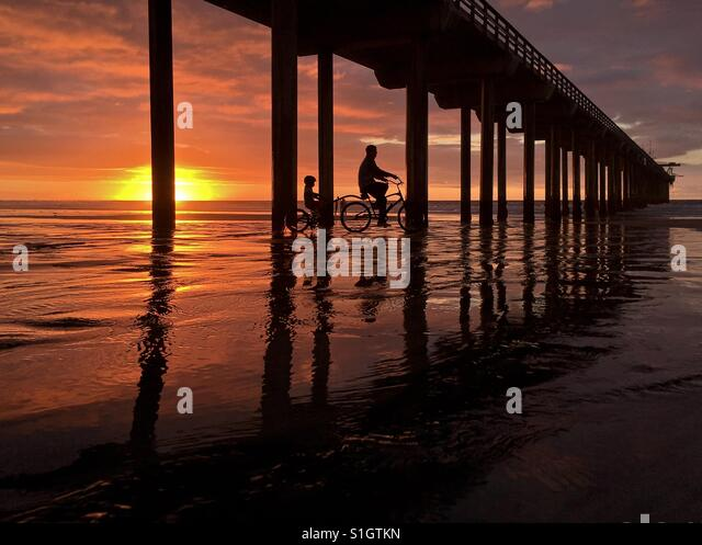 Silhouette of two bicycle riders riding under a beach pier in La Jolla, California, USA. - Stock-Bilder