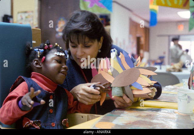 New Jersey East Orange Cerebral Palsy Center disabled student therapist Black girl arts and crafts - Stock Image