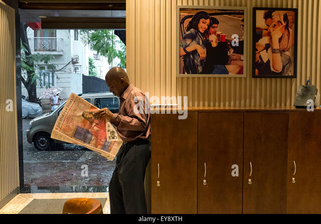 A man is seen reading a newspaper in a coffee shop in Mumbai - Stock Image