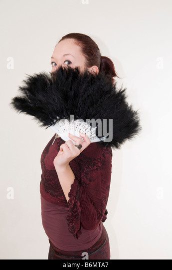 young Gothic teen hiding behind a black feathered fan Model Release Available - Stock Image