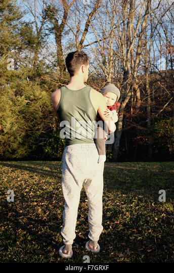 Man from behind holding baby boy - Stock Image
