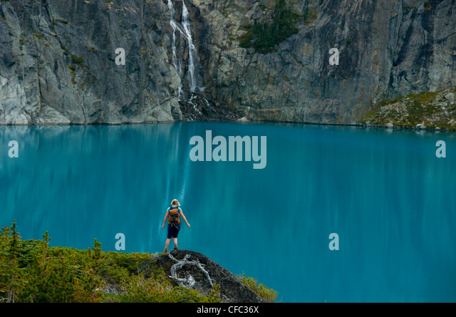 A young woman hikes in front of a blue lake and waterfall in the Niut Range, British Columbia, Canada - Stock-Bilder
