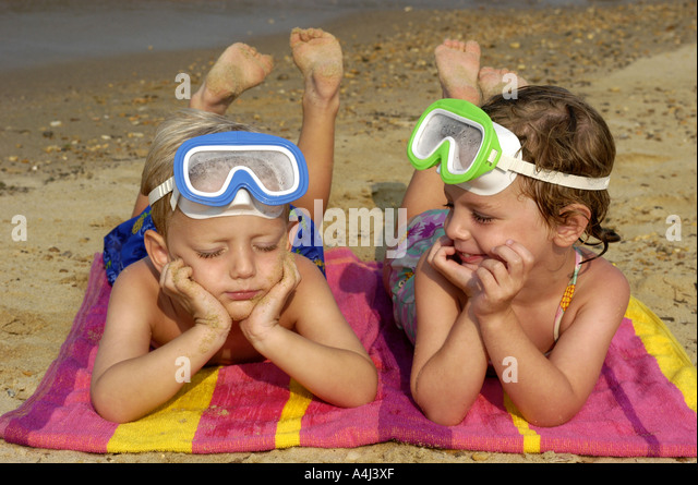 Children kids boy and girl twins age 4 beach beaches fyoung family summer vacation - Stock Image