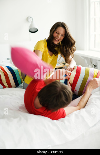 A young couple having a pillow-fight. - Stock-Bilder